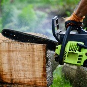 A chainsaw cutting of a plank from a log.