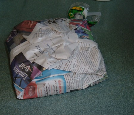 A wrapped newspaper containing green beans.