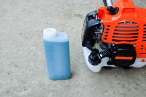 A two-stroke gas next to a trimmer.