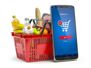A basket of groceries next to a smartphone.