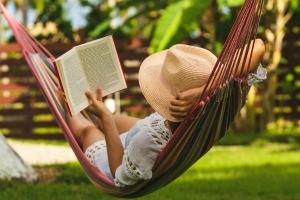 A woman reading in a hammock.