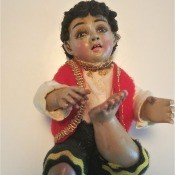 Identifying a Porcelain Figurine? - sitting figurine of a boy with foot up and wearing gold trimmed red vest
