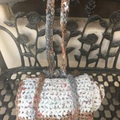 DIY Crochet Plarn Sleeping Mats - finished sleeping mat tied closed and sitting on a wrought iron bench with the handle looped over the back of the bench