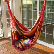 A hammock swing hanging in a sunny location.
