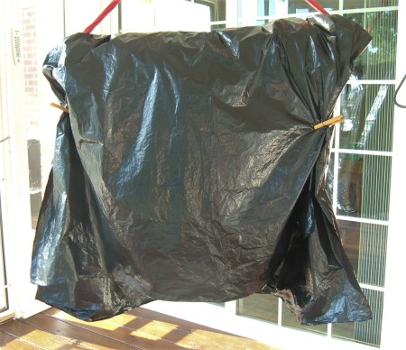 A plastic garbage bag covering a hanging hammock.