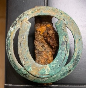 Identifying an Old Equipment Emblem? - corroded circle with horseshoe emblem or? with a rusty mount on the back
