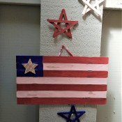A wooden stick flag with wooden stars in red, white and blue.