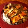 A serving of chicken katsu curry on a plate.