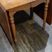 A dining table with the sides down.