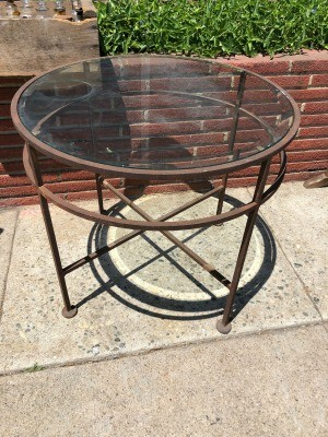 A wrought iron table with a glass top.