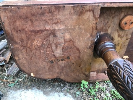 The bottom of an old table with a carved leg.
