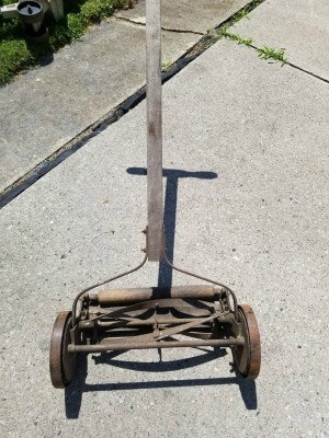 A old reel mower on a concrete surface.
