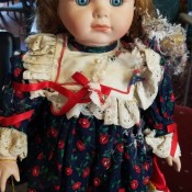 A porcelain baby doll with reddish hair and blue eyes.