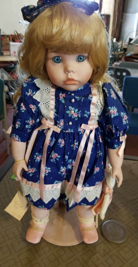 A porcelain doll of a young girl with blue eyes and blonde hair.