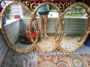 A three panel mirror with a gilt frame.