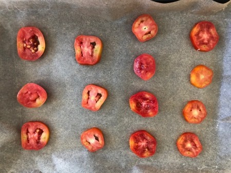 A cookie sheet of halved Roma tomatoes.