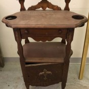 Value of an Antique Side Table? - antique table with two circular holes with lower ridge in the top, a shelf and lower storage cabinet, and a narrow shelf that is raised above the level of the table top, plus a drawer