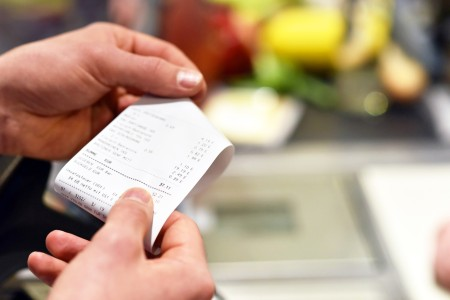 A woman looking at her shopping receipt.