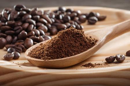 Ground coffee next to coffee beans.