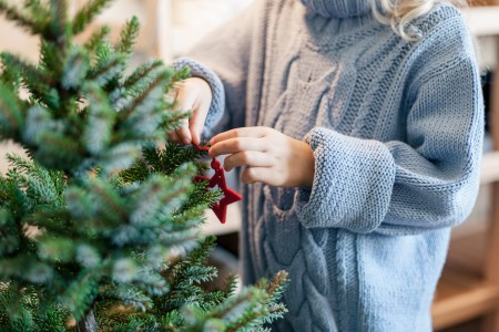 A small Christmas tree being decorated.