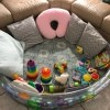 The baby pool with pillows and toys for playtime.
