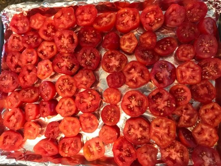 A cookie sheet of tomato slices.