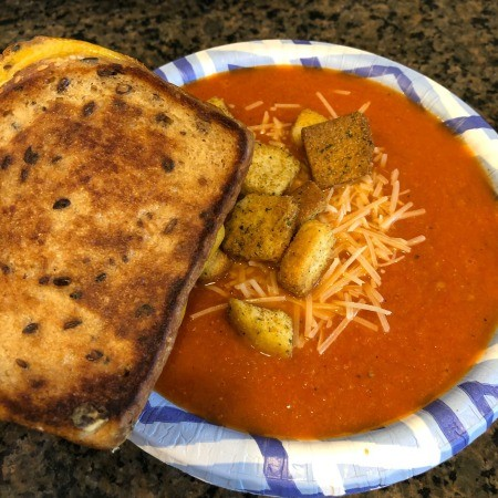 A bowl of tomato soup with a grilled cheese sandwich.