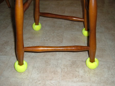 Chair legs with yellow tennis balls on the bottom.