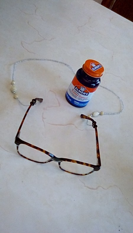 A pair of glasses attached to a neck chain with rubber cement.