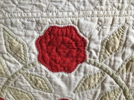 An old quilt done in white and red.