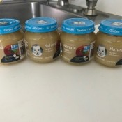 Four jars of baby food on a counter.