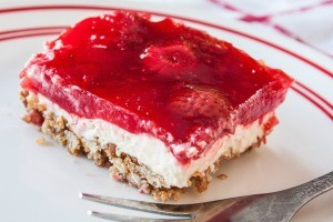 A square of pretzel salad with a strawberry jello topping.