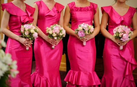 A row of bridesmaids in pink dresses.