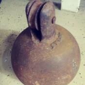 Identifying Old Equipment? - rusty flat bottomed iron ball with a pulley style wheel mounted on top