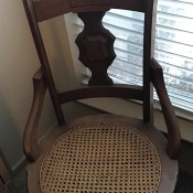 An antique chair with a cane seat.