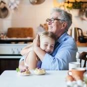 A grandmother hugging her grandchild.