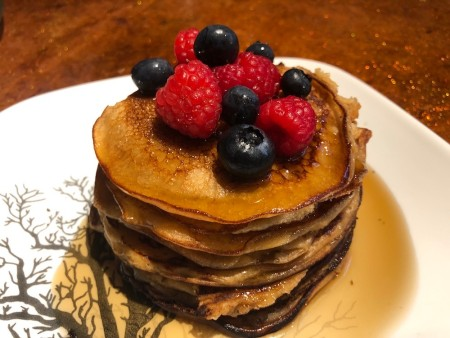 A stack of pancakes with syrup and fruit on the top.
