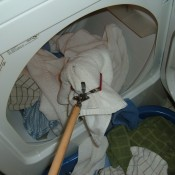 Grabbing laundry from the dryer with a reach extender.