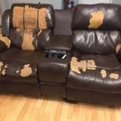 A leather couch with many worn spots.