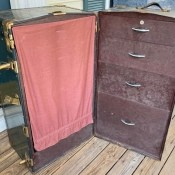 An open steamer chest with drawers.