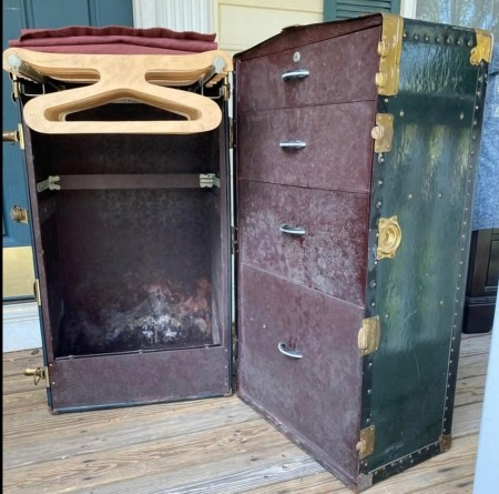 An open steamer chest with hangers and drawers.