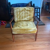 A wooden chair with a yellow cushion.