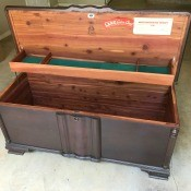 A wooden cedar chest with the lid open.