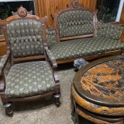 An antique chair with matching loveseat and a coffee table.