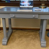 A grey desk with a drawer in the front.
