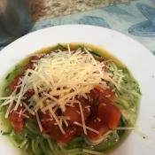 A completed dish of zucchini spiral noodles with fresh tomato sauce and cheese.