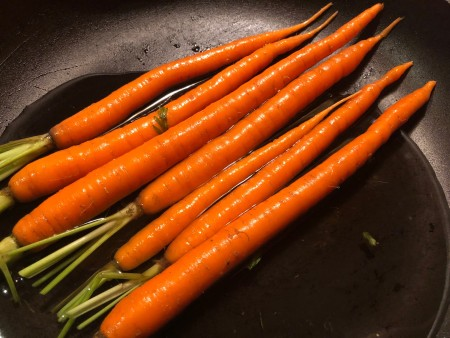 Whole carrots in a frying pan.