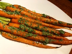 A plate of roasted carrots with carrot-top pesto.
