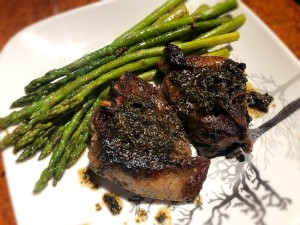 A plate of lamb chops with asparagus.