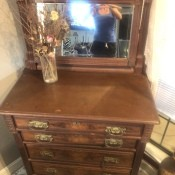 An antique dresser with a mirror.